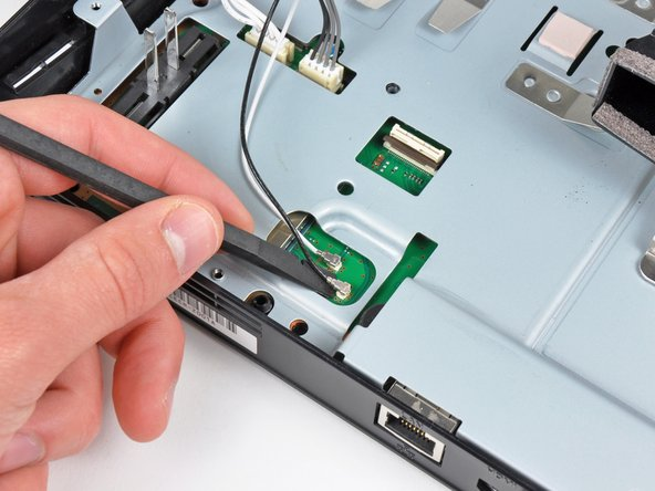 Image 1/2: Use the flat end of a spudger to pry both antenna connectors up from their sockets on the motherboard.