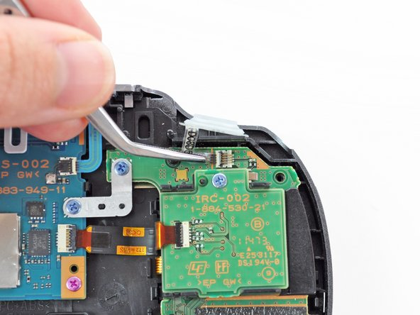 Using tweezers, slide the flex cable out of the socket. Do not pull on the black tab! Instead, pull the thin flex cable away from the connector (to the left in this image).