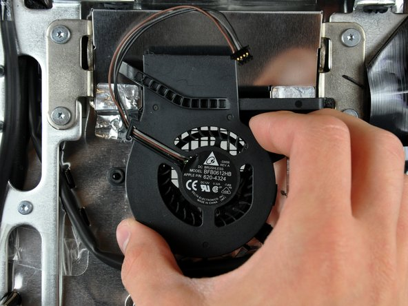 Gently lift the hard drive fan off the plastic posts protruding from the rear case.