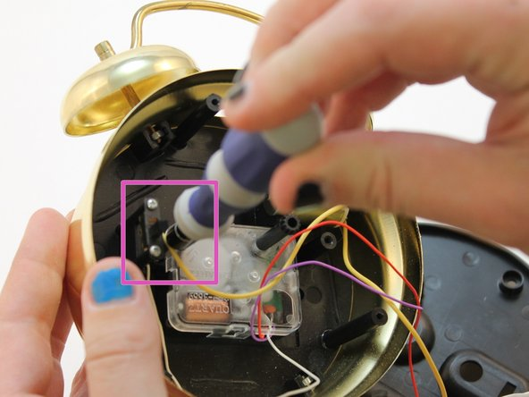 Using a screwdriver #1, remove the 2 small screws located at the top and bottom of the alarm switch.