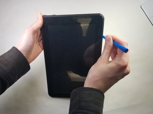 Using the plastic opening tool, insert it into the crease where the glass screen meets the housing of the rest of the tablet. Once inserted, keep inserted and run along the edges to separate the plastic clips from each other to dislodge the back plastic away from the glass and internal components.