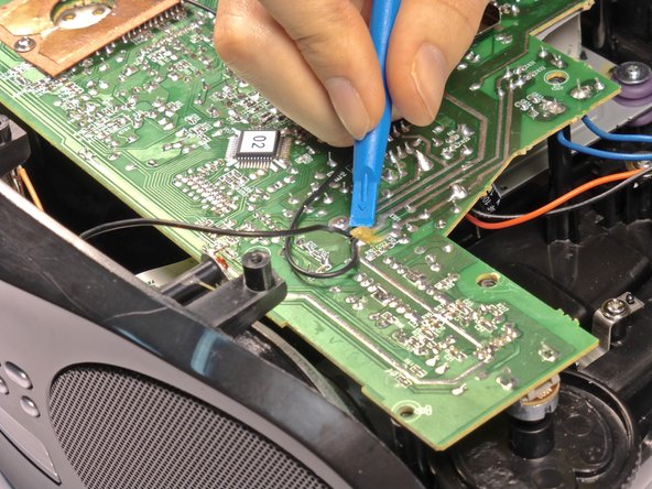 Scrape off the glue from the black wire with the blue plastic opening tool.