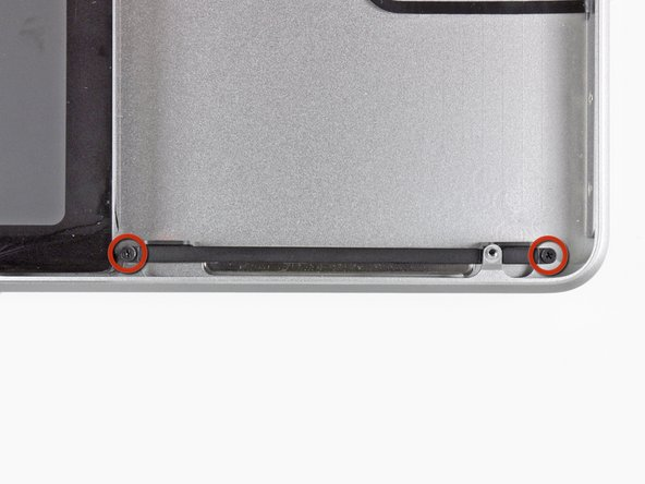Remove the two 10 mm Phillips screws securing the front hard drive bracket to the upper case.