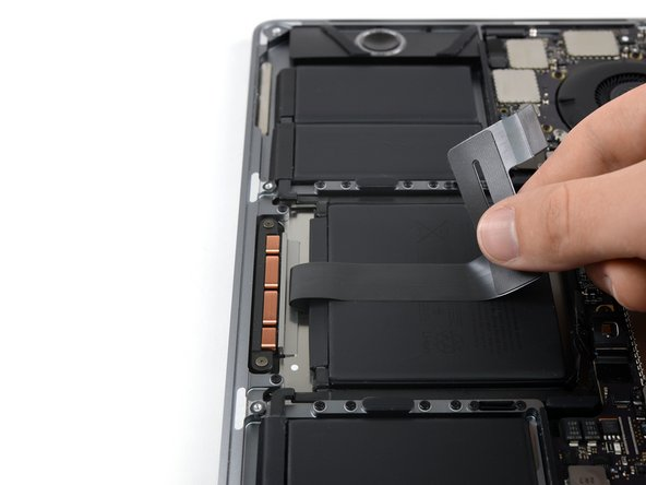 Carefully peel the trackpad ribbon cable up off the battery, and push it out of the way.