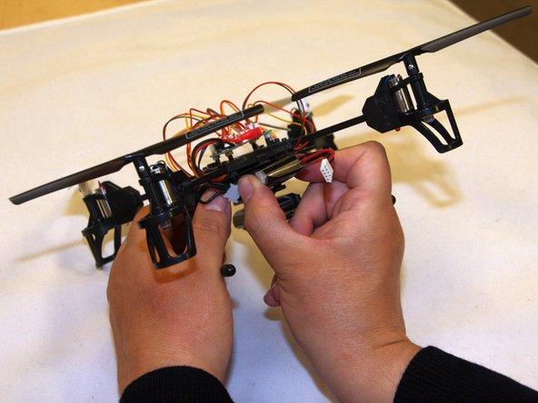 Locate the drone battery housed in the slot between the drone body and the camera.