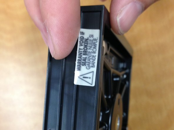 Note the label:  Warranty Void If Seal Broken.  In this case, we want to retrieve the data and do not care about the warranty.  Remove the label, to expose one of the four total screws on the side to remove the internal drive.
