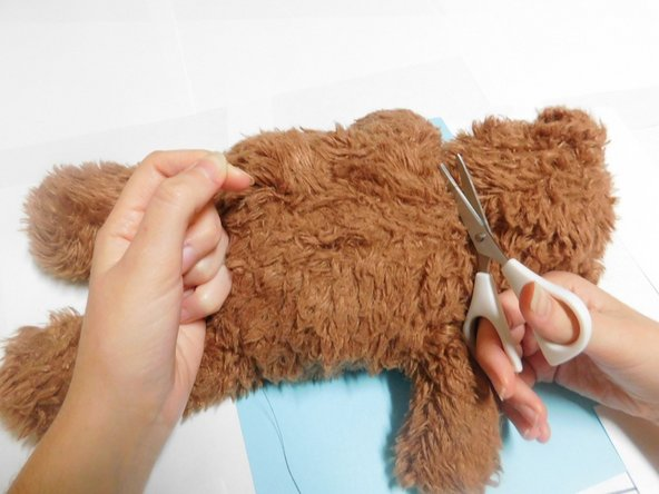 The excess thread can be hidden by running your needle inside the fabric and back out an inch away, cutting the thread close to the surface of the fabric, and then tugging on the fabric to make the end of the thread disappear inside the stuffed animal.