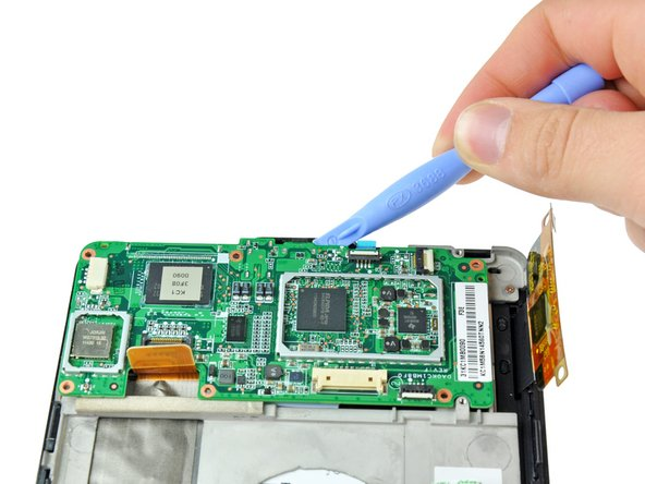 Image 2/3: Lift the motherboard out of the Kindle Fire, making sure that the power button cable from step 8 comes free from its connector.