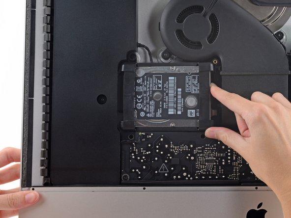 Soulevez le disque dur par le bord le plus proche de la carte mère et tirez-le légèrement hors de son logement.