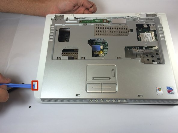 Insert the plastic opening tool in between the back and front plates of the laptop