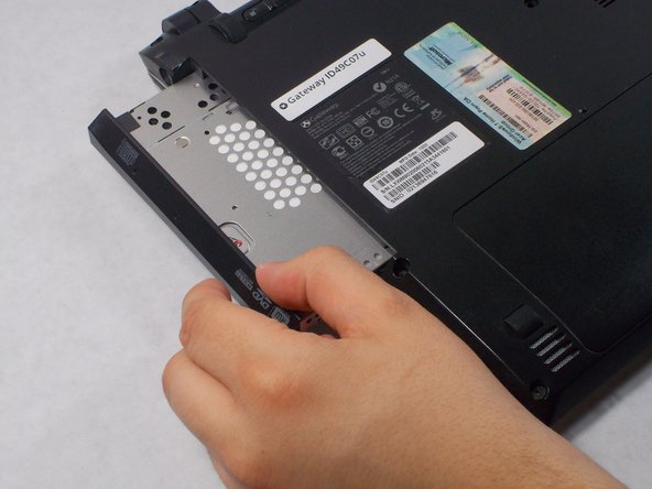 Image 3/3: Once loosened, use your hand to pull the DVD drive out.