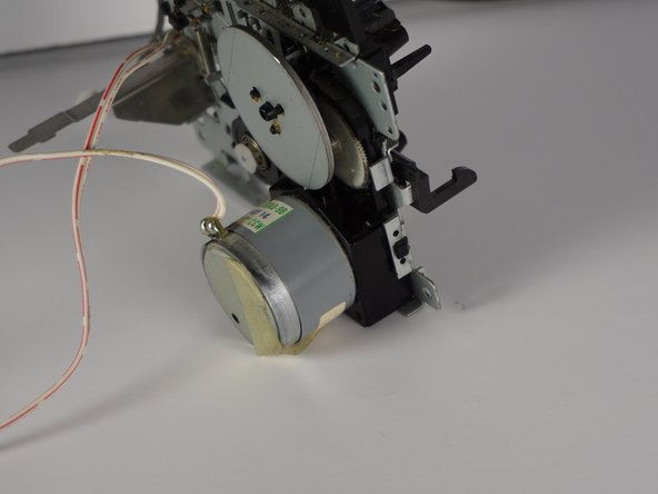 Image 2/3: Note the small latch on the side of assembly as you remove the motor.