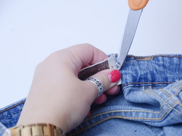Push the elastic strip along the waistband through the other cut using the safety pin as an aid.