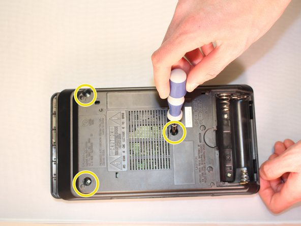Image 1/3: Remove both of the screws from the battery compartment.