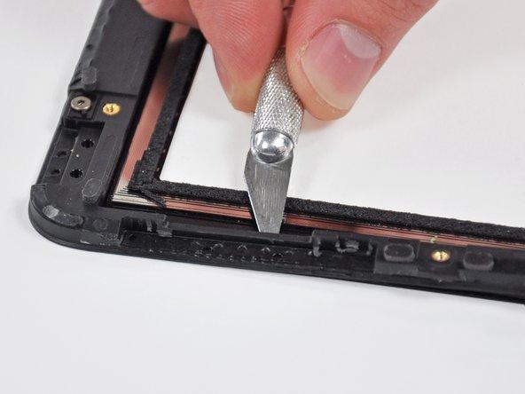稍微加热橡胶黏住区域。使用塑料撬棒将塑料支架与前玻璃面板分开,以进入橡胶黏住区域。