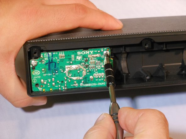 Using the Phillips #1 screwdriver, remove the two 6mm screws holding the AUX board in place.