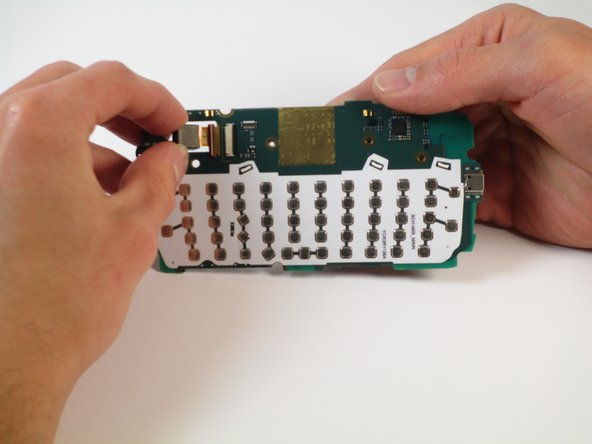 Image 1/1: The metal foil connector attached to the camera should slide out of the motherboard.