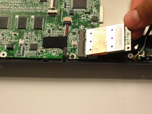 Image 1/1: Gently pull the wifi card to the right and out of its housing.