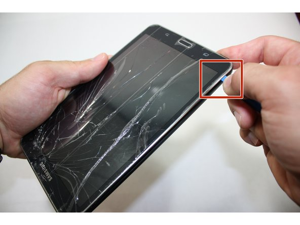 Starting at any corner, insert the pry tool between the chrome screen frame and black phone housing.