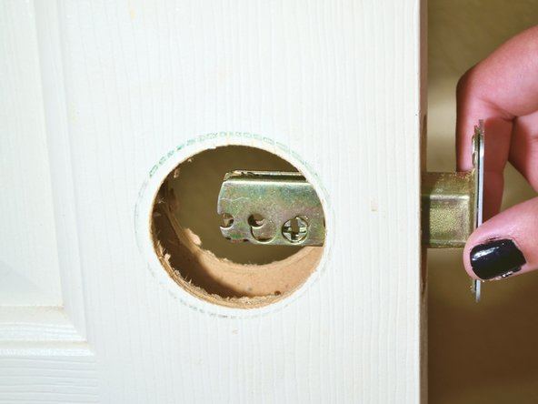 Slide the latch of the deadbolt back into the door frame.