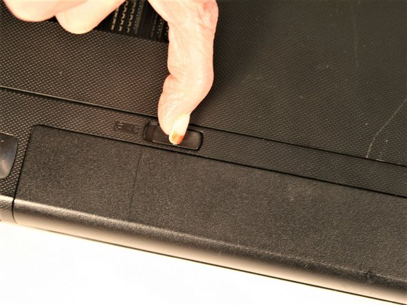 Move the left tab to the left. This will release the battery. You will hear an audible 'click' and see the battery separate from the rest of the laptop.