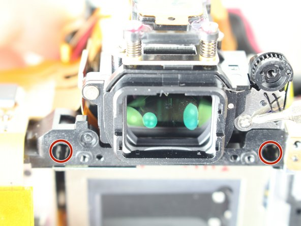 Remove two screws from just below and to the sides of the viewfinder.