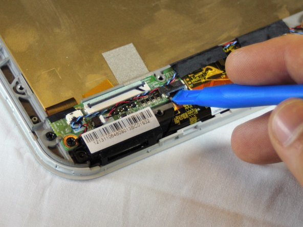 Image 1/2: Gently use the spudger to remove the ribbon cable.