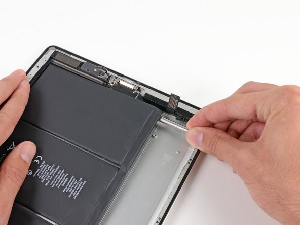 Image 1/3: As you push the spudger further underneath the battery, keep it as flat against the rear case as possible to avoid bending the battery.