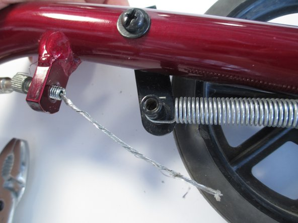 Unhook the spring connecting the brake shoe to the wheel.