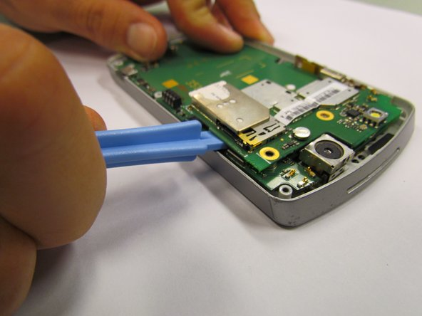 Remove the glued, mounted surface by lifting it from underneath the SIM card slot by using the plastic opening tool.