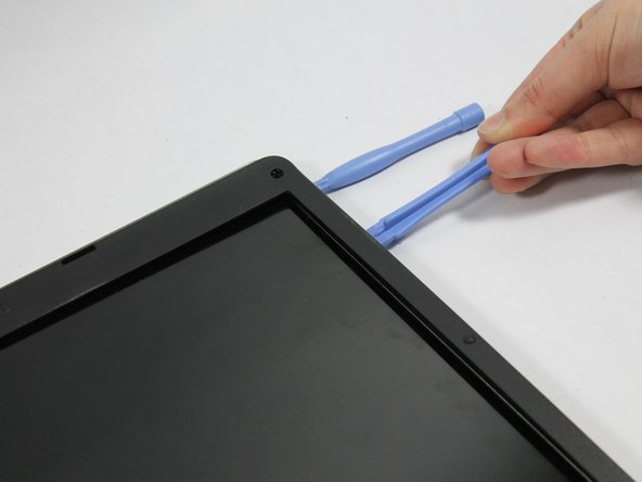 Using the plastic prying tools separate the plastic surrounding the screen