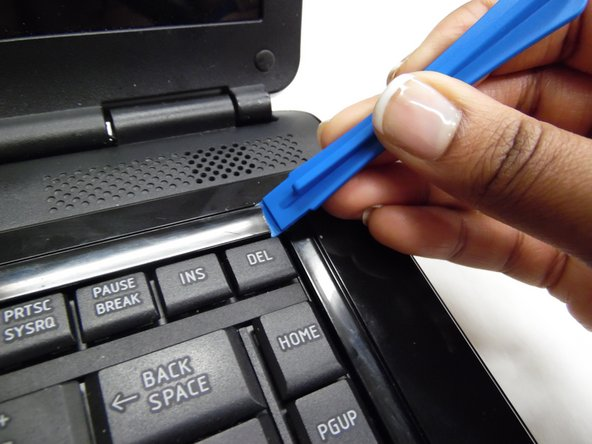 Use a plastic opening tool to lift out keyboard lining portion located at the top of the keyboard.