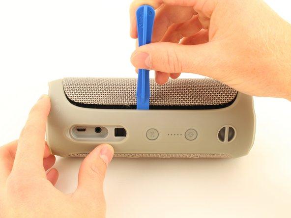 Führe das Öffnungswerkzeug in den Spalt zwischen der Abdeckung und dem Gummiboden ein. Achte darauf das die Box so steht, das die Akku-LEDs links neben den An/Aus Knopf sind.