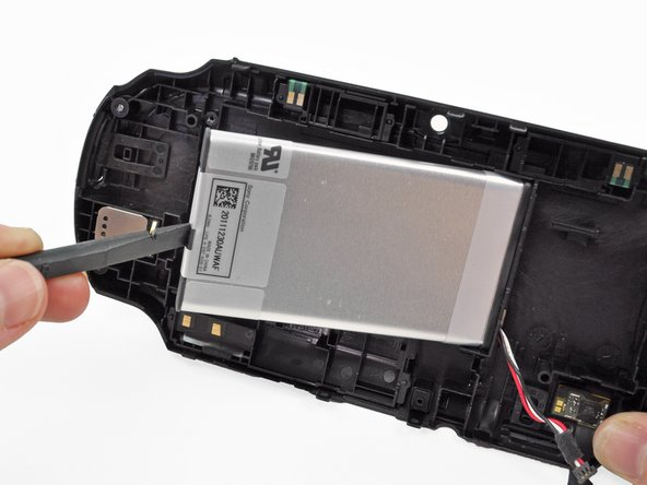 Image 2/3: Guide the battery wires through the hole in the back casing as you remove the battery.