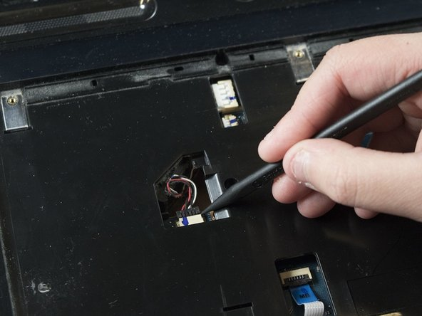 Disconnect the wire connector by using the flat end of spudger to gently pry it apart from the connection point.