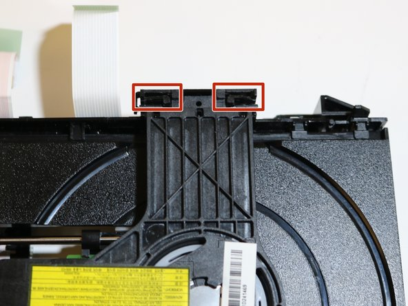 Locate the two black tabs, found at the end of the black bar across the disc tray. The tabs are located on the opposite side of the spring.