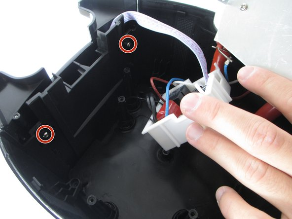 Using your other hand, use the Philips 2 Screwdriver to unscrew the two 8-mm screws labeled in a red outline. They are located inside the base on the front end of the Brew Station.