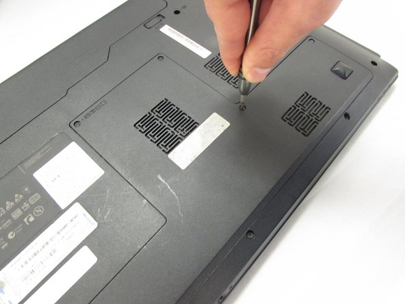 Using the Phillips #00 Screwdriver,  Loosen the five 5.4 mm screws around the back panel from the laptop.