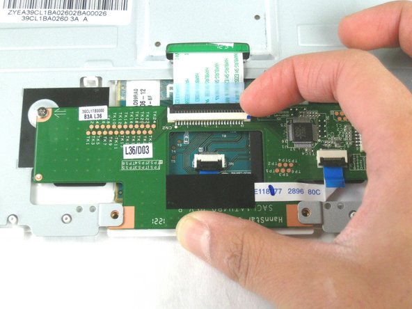 Image 1/3: Unplug the ribbon cable between the touchpad and the mouse buttons controller.