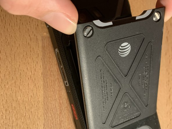 After unscrewing them, lift up the protective back shield and put it to the side.