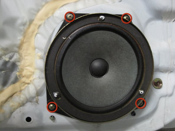Remove the four Phillips screws that hold the speaker in the door.