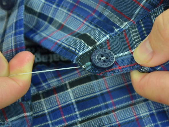 Pull the thread taut, until the button lays flat on the fabric.