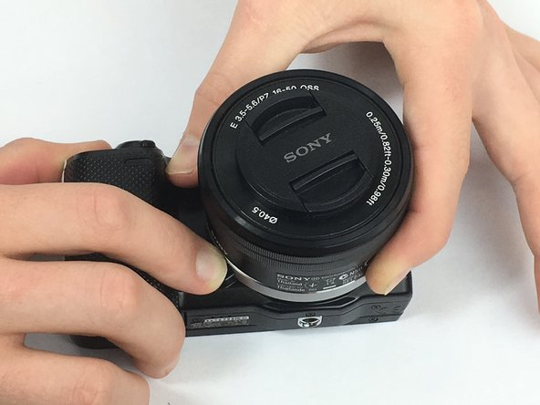 While holding down the button, twist the lens counter-clockwise until you hear and feel a firm click.