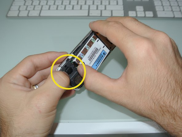 slide the black button to free the battery so you can grab it with your other hand.