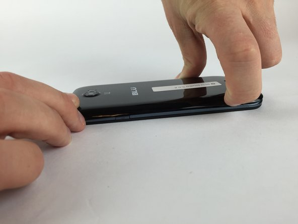 Image 1/2: Once the case is lifted on the corner, slide your finger along the edge of the phone to remove the rest of the case.