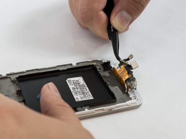Using tweezers peel back the glued down ribbon cable at the bottom of the phone.