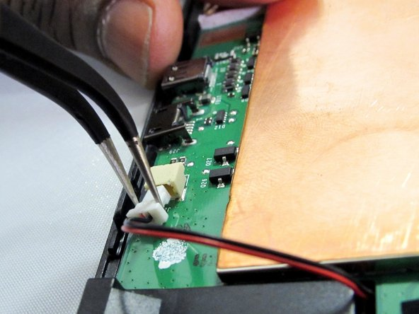Remove the red and black wire connector from the motherboard using either fingers or tweezers.
