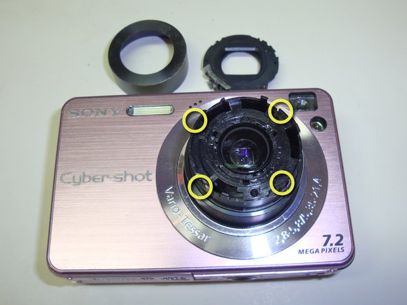 Image 3/3: Once the shutter has been removed, the outer lens is exposed completely.  This is a great opportunity to clean any fingerprints or anything else which might be on it.  If you are extremely careful, the inner lens can also be accessed through the openings around the edge.