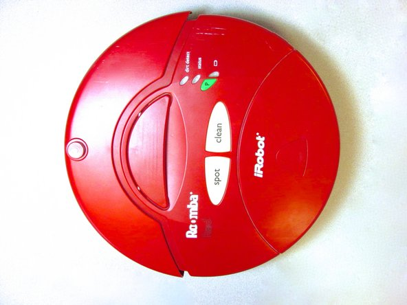 Lay the Roomba on a flat surface with the red side up.