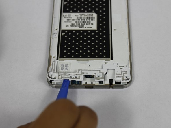 Using a plastic opening tool, remove the antenna extender from the mid-frame.